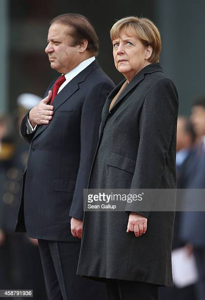 German Chancellor Angela Merkel and Pakistani Prime Minister Nawaz Sharif listen to their countries' respective national anthems upon Sharif's...