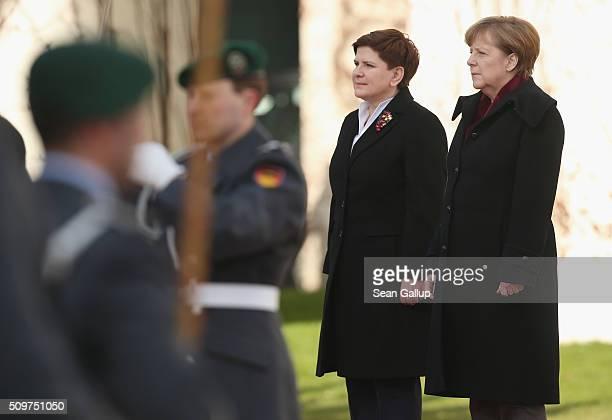 German Chancellor Angela Merkel and Polish Prime Minister Beata Szydlo listen to their countries' resepective naitonal anthems upon Szydlo's arrival...