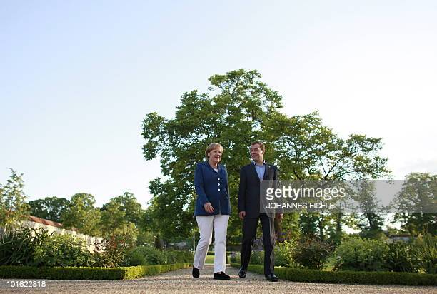 German Chancellor Angela Merkel and Russian President Dmitry Medvedev take a walk in the garden during talks at Meseberg Palace the government's...
