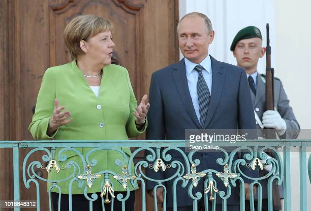 German Chancellor Angela Merkel and Russian President Vladimir Putin chat upon his arrival at Schloss Meseberg palace the German government retreat...