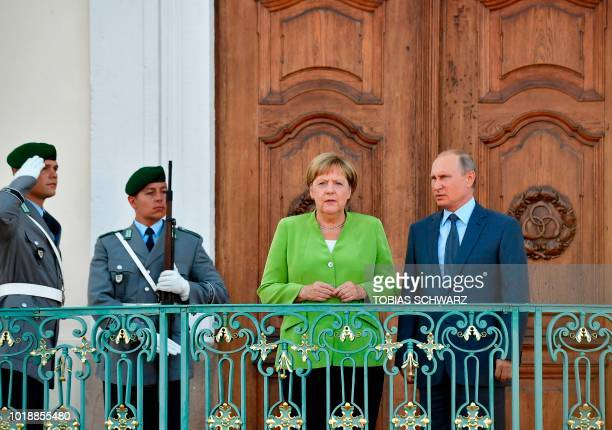 German Chancellor Angela Merkel and Russian President Vladimir Putin react as they pose for the media on August 18 2018 at Schloss Meseberg castle in...