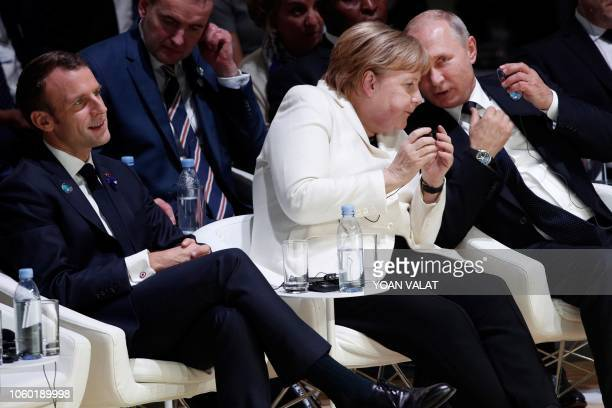 German Chancellor Angela Merkel and Russian President Vladimir Putin speak together as they attend next to French President Emmanuel Macron the...