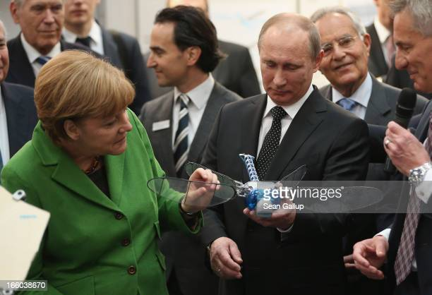 German Chancellor Angela Merkel and Russian President Vladimir Putin look at a remotecontrolled drone called a BionicOpter that looks like a...