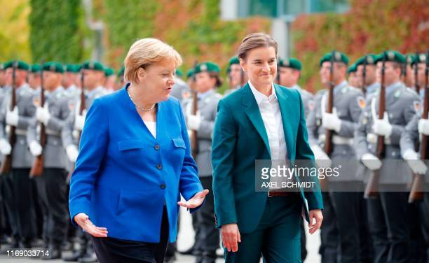 German Chancellor Angela Merkel and Serbian Prime Minister Ana Brnabic inspect a military honor guard during a welcoming ceremony in front of the...