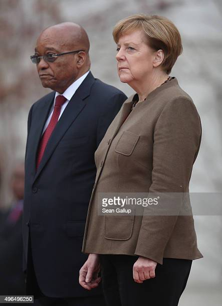 German Chancellor Angela Merkel and South African President Jacob Zuma listen to their countries' national anthems upon Zuma's arrival at the...