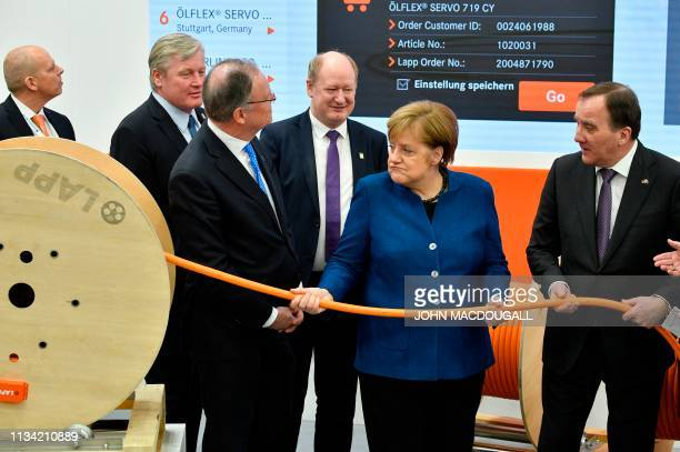 German Chancellor Angela Merkel and Swedish Prime Minister Stefan Lofven pull a cable that is fitted with a selfmeasuring app at the stand of Lapp as...