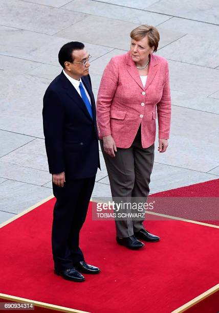 German Chancellor Angela Merkel and the Chinese Prime Minister Li Keqiang stand on a podium to listen to the national anthems at the Chancellery in...