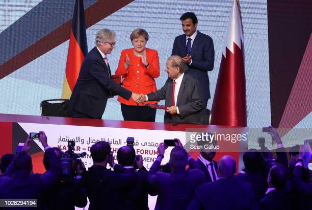 German Chancellor Angela Merkel and the Emir of Qatar Sheikh Tamim bin Hamad Al Thani look on at the signing of a memorandum of understanding between...
