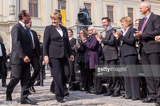 German Chancellor Angela Merkel and the French president Francois Hollande are applauded during the ceremony on the occasion of the 50th anniversary...