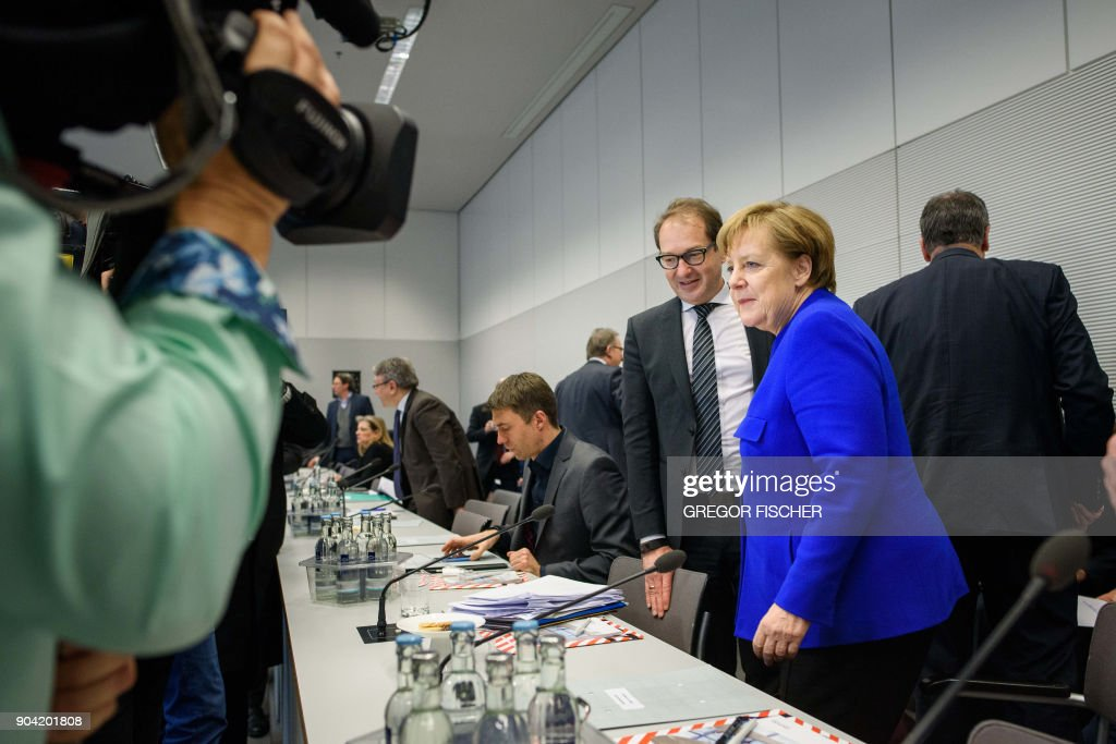 German chancellor Angela Merkel (R) and the leader of the regional faction of the Christian Social Union (CSU) Alexander Dobrindt arrive for a parliamentary group meeting of the Christian Democratic Party (CDU) and the CSU at the Reichstag parliament building in Berlin. / AFP PHOTO / dpa / Gregor Fischer / Germany OUT