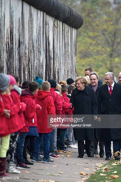 German chancellor Angela Merkel and the mayor of Berlin Klaus Wowereit welcome children at the Berlin Wall Memorial at Bernauer Strasse on the 25th...