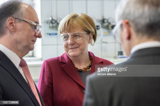 German Chancellor Angela Merkel and the State Premier of the federal state of SaxonyAnhalt Reiner Haseloff tour an analytical laboratory at the...
