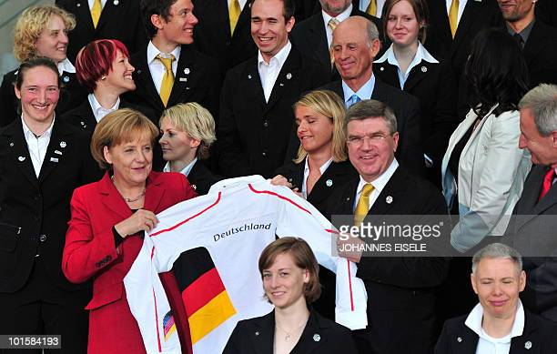 German Chancellor Angela Merkel and Thomas Bach head of German Olympic Sport Association pose with a jacket of the German Olympic Team Merkel...