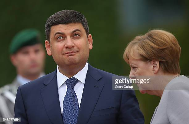 German Chancellor Angela Merkel and Ukrainian Prime Minister Volodymyr Groysman prepare to review a guard of honor upon Groysman's arrival at the...