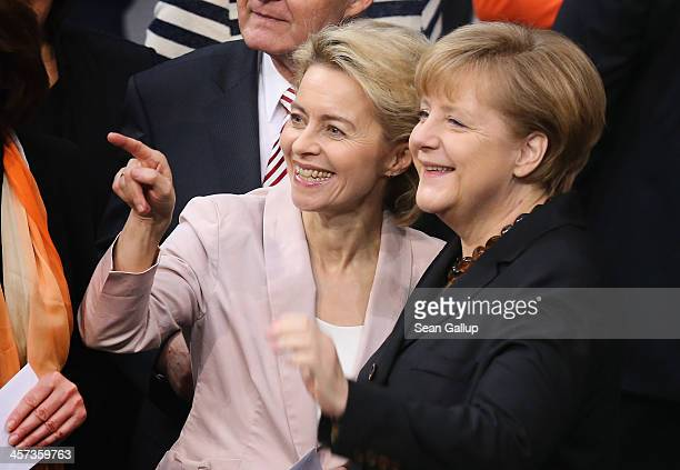 German Chancellor Angela Merkel and Ursula von der Leyen who will become Germany's new Defense Minister chat during a vote at the Bundestag over her...