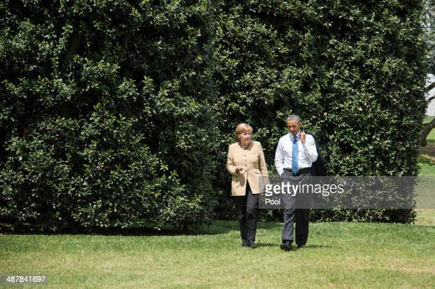 German Chancellor Angela Merkel and US President Barack Obama chat as they walk on the White House grounds May 2 2014 in Washington DC Obama and...