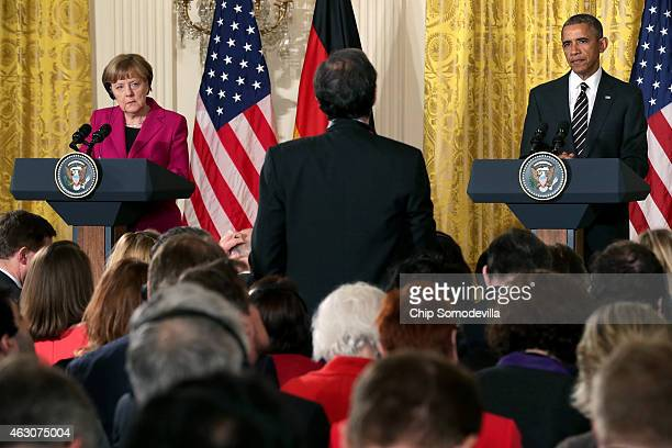 German Chancellor Angela Merkel and US President Barack Obama listen to a journalist's question as they hold a joint news conference in the East Room...