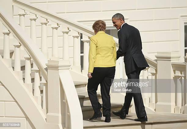German Chancellor Angela Merkel and US President Barack Obama walk up the steps at Schloss Herrenhausen palace upon Obama's arrival on April 24 2016...
