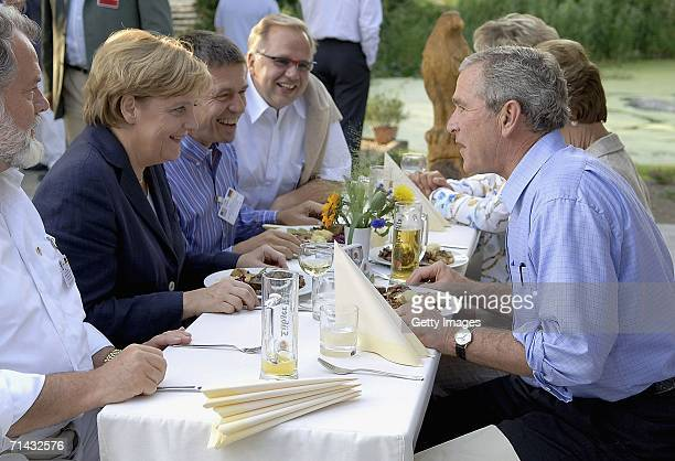 German Chancellor Angela Merkel and U.S. President George W. Bush eat during a barbecue July 13, 2006 in Trinwillershagen near Stralsund, Germany....