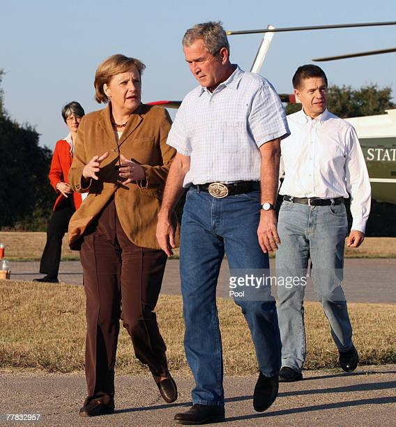 German Chancellor Angela Merkel and US President George W Bush walk with her husband Dr Joachim Sauer upon their arrival to his ranch November 9 2007...