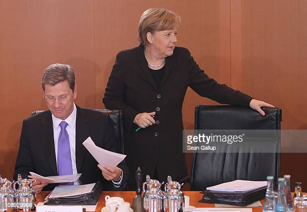 German Chancellor Angela Merkel and Vice Chancellor and Foreign Minister Guido Westerwelle arrive for the weekly German government cabinet meeting at...