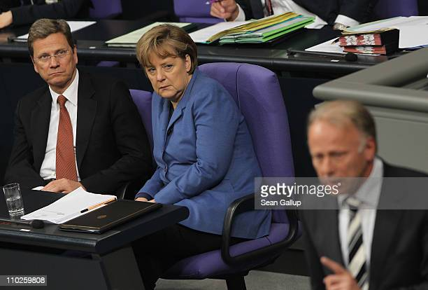 German Chancellor Angela Merkel and Vice Chancellor and Foreign Minister Guido Westerwelle listen to German Greens Party Bundestag faction coleader...