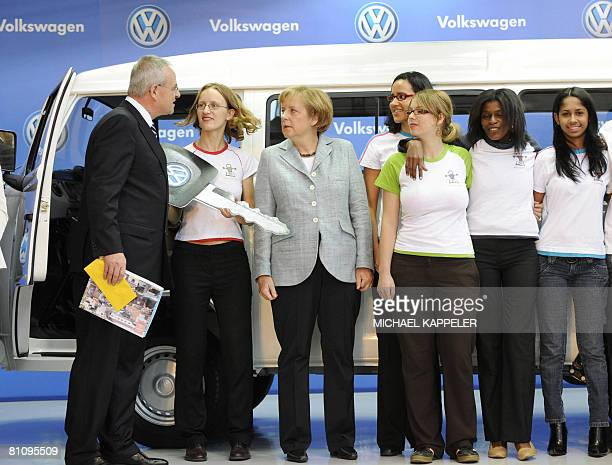 German Chancellor Angela Merkel and Volkswagen CEO Martin Winterkorn present a new VW bus to Daniela Mattern from Germany for the Social project...