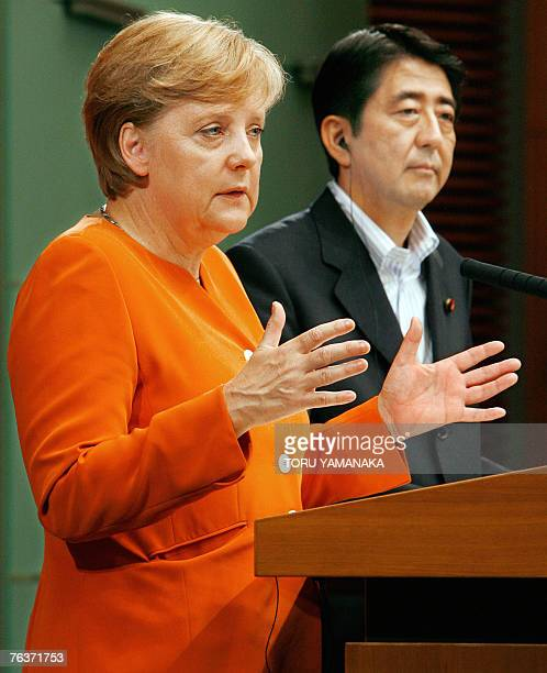 German Chancellor Angela Merkel answers a question while Japanese Prime Minister Shinzo Abe looks on during their joint press conference after their...
