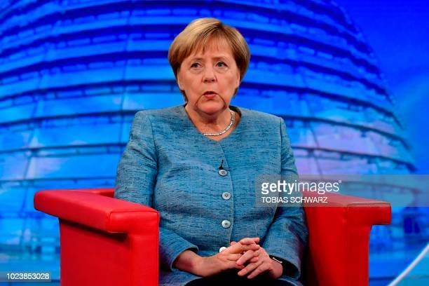 German Chancellor Angela Merkel answers German journalist Tina Hassel's questions during her traditional summer interview at a TV studio of German...