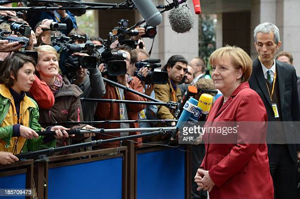 German Chancellor Angela Merkel answers journalists' questions on October 24 2013 as she arrives to attend a European Council meeting at the EU...