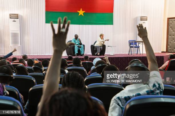 German Chancellor Angela Merkel answers questions with head of German department of the university of Ouagadougou JeanClaude Naba during a meeting...