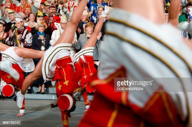 German Chancellor Angela Merkel applauds as she watches a performance of carnival dancers as she receives 'royal couples' of the federal German...