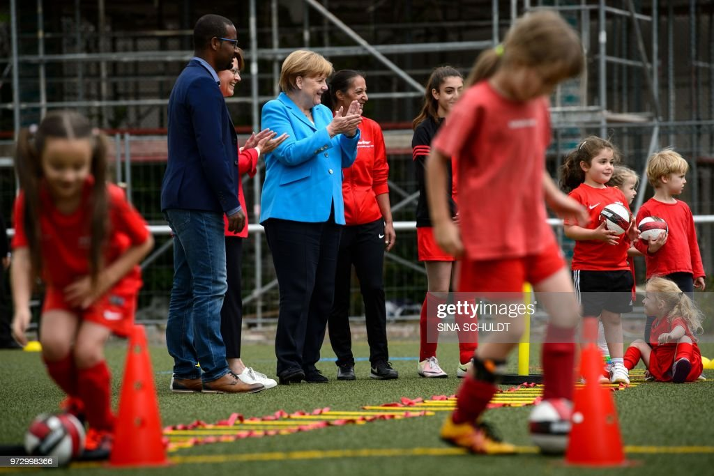 German Chancellor Angela Merkel (C) applauds children taking part in the event 'Sports and Integration' as she visits the 'SV Rot-Weiß Viktoria Mitte 08' sports club in Berlin on June 13, 2018, prior to the German government's integration summit. (Photo by Sina Schuldt / dpa / AFP) / Germany OUT