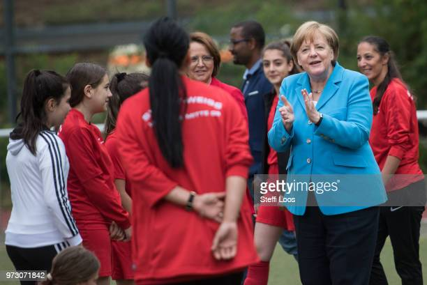 German Chancellor Angela Merkel applauses during a visit of a program to encourage integration of children with foreign roots through football at the...