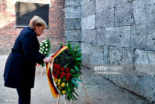 German Chancellor Angela Merkel arranges the ribbon of a wreath as she attends a wreath laying ceremony at the Death Wall during her visit at the...
