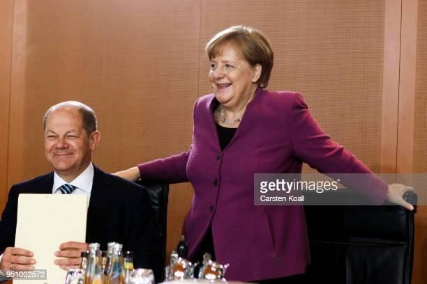 German Chancellor Angela Merkel arrives beside Finance Minister and Vice Chancellor Olaf Scholz for the weekly government cabinet meeting on April 25...