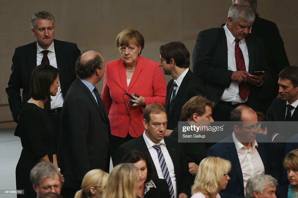 German Chancellor Angela Merkel (in red) arrives to cast her ballot during votes over the third EU financial aid package to Greece at an extraordinary session of the German parliament, the Bundestag, on July 17, 2015 in Berlin, Germany. The Bundestag is among several European parliaments that must vote on whether to allow negotations over the aid package that will help Greece to avert state bankruptcy and shore up the Greek banking system.