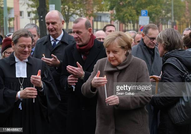 German Chancellor Angela Merkel arrives to place a candle at a memorial to the Berlin Wall at Bernauer Strasse following a ceremony to celebrate the...