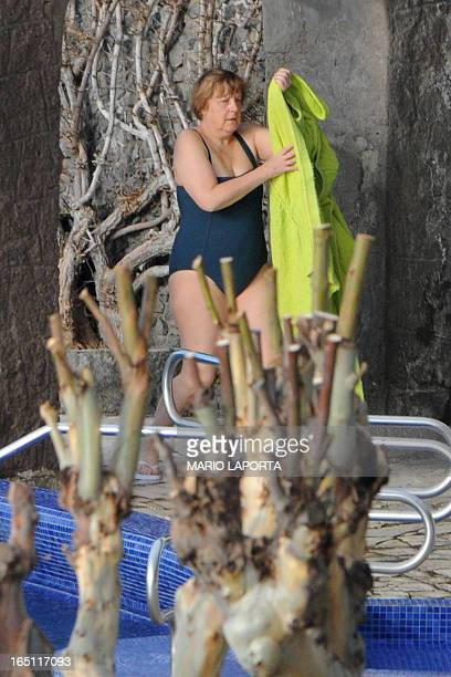 German Chancellor Angela Merkel arrives to take a bath in the swimming pool of the Aphrodite Terme in the coastal town of Sant'Angelo d'Ischia on the...