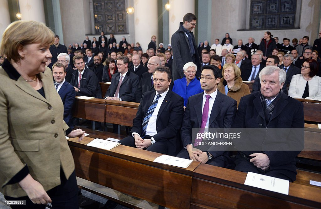 German Chancellor Angela Merkel arrives to take her seat next to German Interior Minister Hans-Peter Friedrich, German Economy Minister and vice-chancellor Philipp Roesler and Bavaria's State Premier Horst Seehofer a mass service to mark the resignation of Pope Benedict XVI at the St. Hedwig's Cathedral in Berlin on February 28, 2013. The mass coincides with the final hour of Benedict XVI papacy as his powers formally expire at 19:00 GMT.