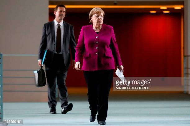 German Chancellor Angela Merkel arrives with her spokesman Steffen Seibert for a news conference after a meeting with governors of eastern German...