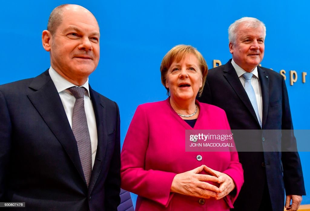 German Chancellor Angela Merkel arrives with Social Democrats party (SPD) leader and designated German Finance Minister and Vice-Chancellor Olaf Scholz (L) and Bavarian Christian Social Union (CSU) leader and designated Interior minister Horst Seehofer at the Federal Press Conference in Berlin, on March 12, 2018 to address a press conference prior to the signature of the chancellor's conservative CDU/CSU and the SPD's coalition contract for a new government. / AFP PHOTO / John MACDOUGALL