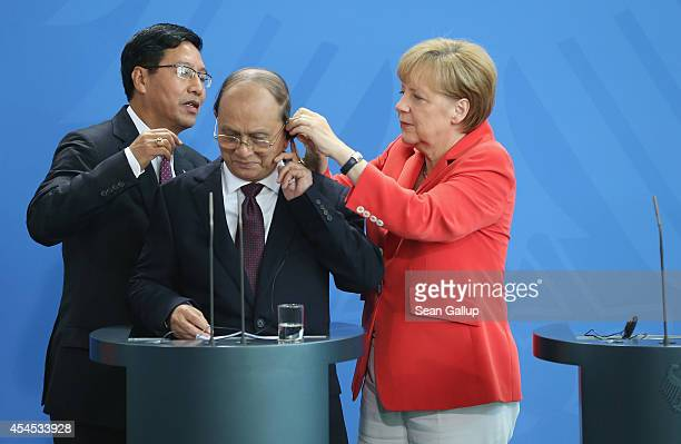 German Chancellor Angela Merkel assists Myanmar President Thein Sein with his headphone prior to speaking to the media following bilateral talks at...
