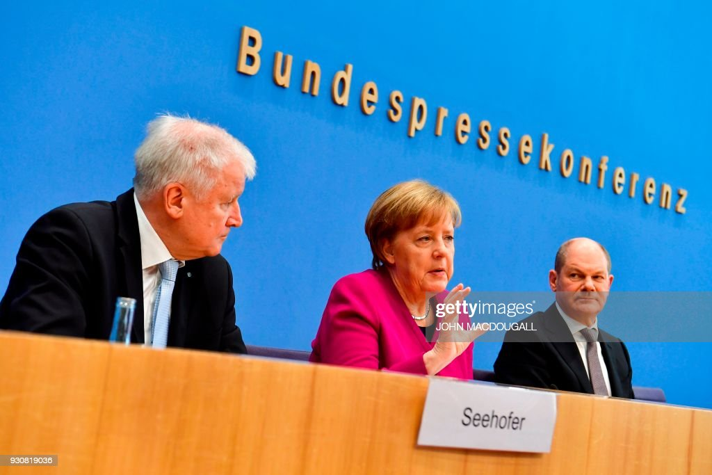 German Chancellor Angela Merkel, Bavarian Christian Social Union (CSU) leader and designated Interior minister Horst Seehofer (L) and Social Democrats party (SPD) leader and designated German Finance Minister and Vice-Chancellor Olaf Scholz (R) address a press conference at the Federal Press Conference in Berlin, on March 12, 2018 prior to the signature of the chancellor's conservative CDU/CSU and the SPD's coalition contract for a new government. / AFP PHOTO / John MACDOUGALL