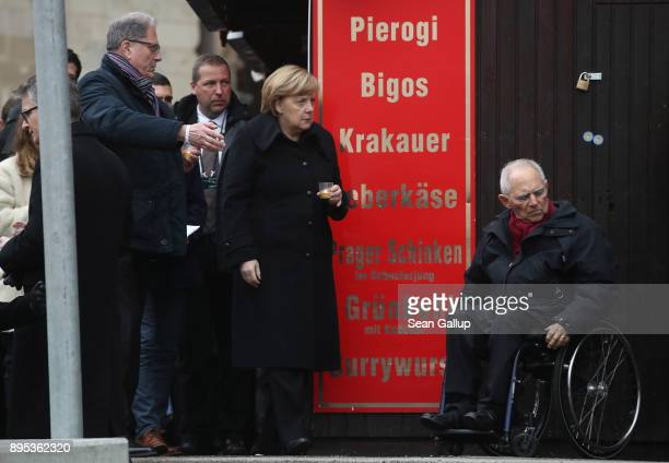 German Chancellor Angela Merkel bears a candle as she and Bundestag President Wolfgang Schaeuble at the inauguration of a memorial to victims at the...