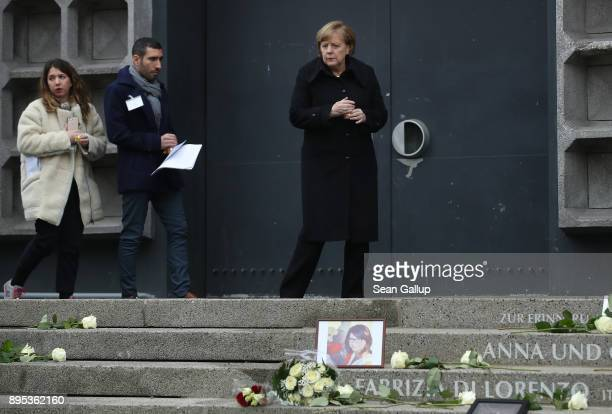 German Chancellor Angela Merkel bears a candle as she arrives at the inauguration of a memorial to victims at the site of the 2016 Christmas market...