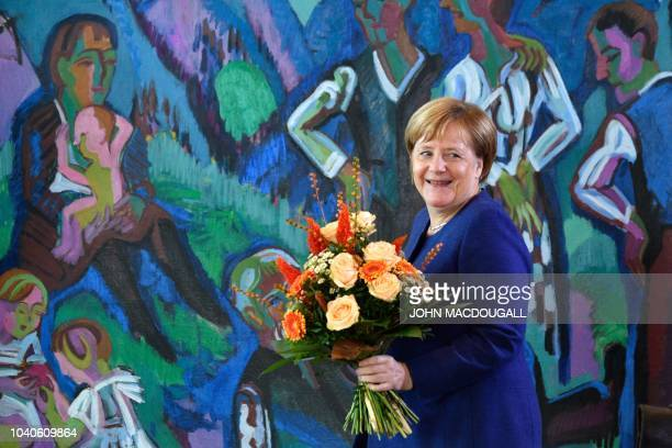 German Chancellor Angela Merkel carries a bouquet of flowers to present it to German Transport Minister Andreas Scheuer for his birthday prior to the...