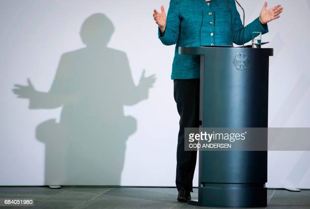 German Chancellor Angela Merkel casts a shadow as she speaks during the national integration awards ceremony at the Chancellery in Berlin on May 17...