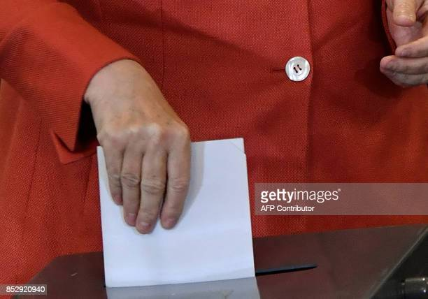 German Chancellor Angela Merkel casts her vote at a polling station in Berlin during general elections on September 24, 2017. Polls opened in Germany...