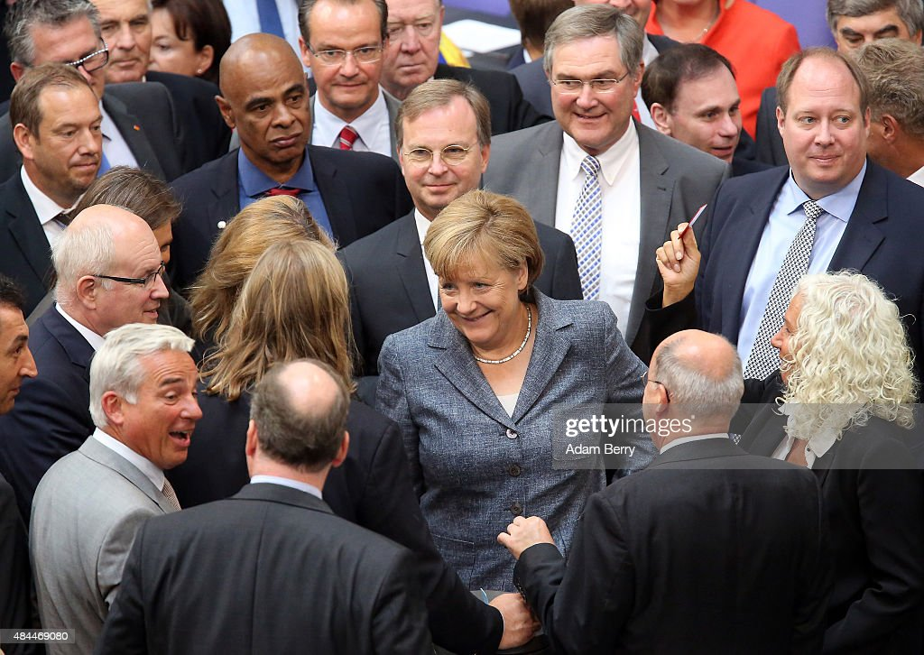 German Chancellor Angela Merkel (CDU) casts her vote on a third bailout package for economically-troubled Eurozone member Greece as she attends a meeting of the German federal parliament, or Bundestag, on August 19, 2015 in Berlin, Germany. European governments vote on the issue this week. Merkel and the country's finance minister, Wolfgang Schaeuble, have encouraged German parliamentarians to support the latest plan, evaluated at 86 billion euros (USD 95.5 billion). Meanwhile the leaders praised the Greek government for accepting German prerequisites for the offer, and have assured that the International Monetary Fund (IMF) would participate in the latest bailout package.